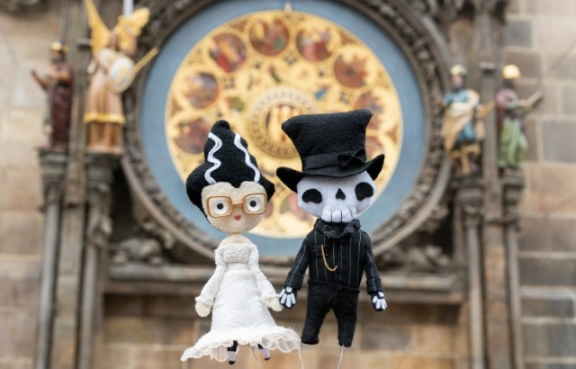 Plush dolls of Frankenstein's Bride and Skull Groom with the Prague astronomical clock