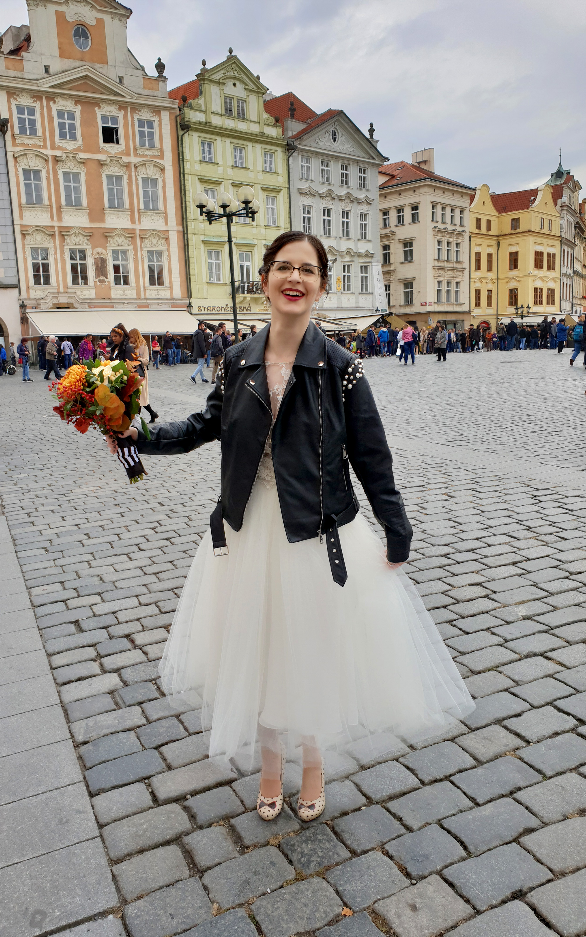 Rock & Roll bride with an autumn bouquet and faux leather jacket. In the Old Town Square