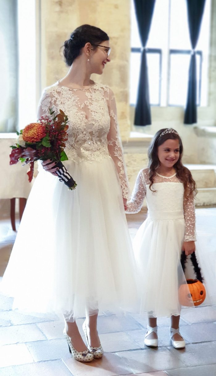 Bride and flower girl at halloween with Trick or Treat pumpkin basket. Orange bouquet and white dresses