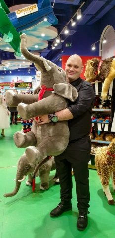 Groom at toy store with stuffed elephant.