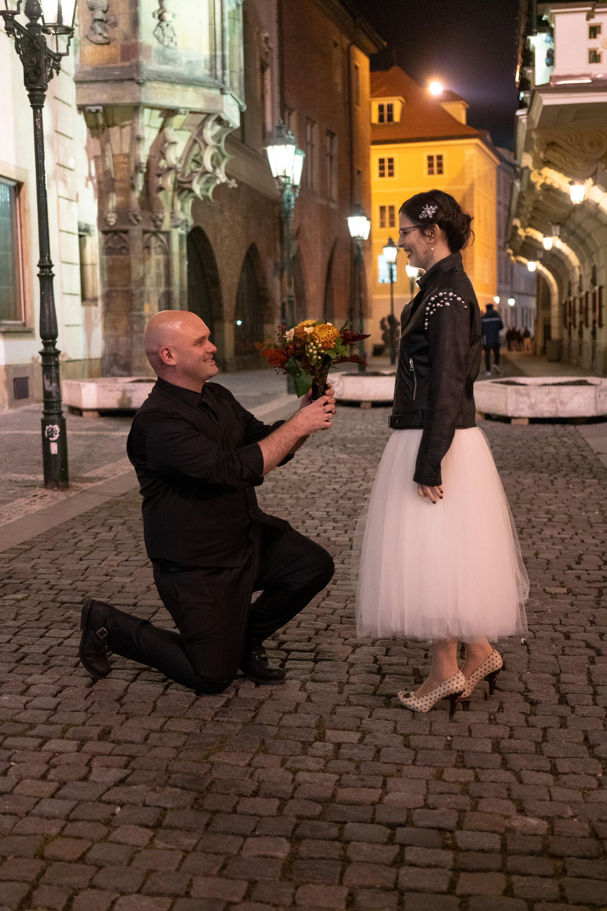 Wedding proposal at night on the streets of old Prague
