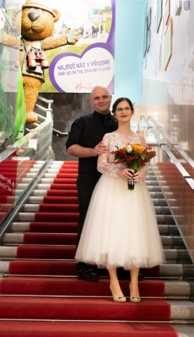 Bride and groom on stairs with red carpet.