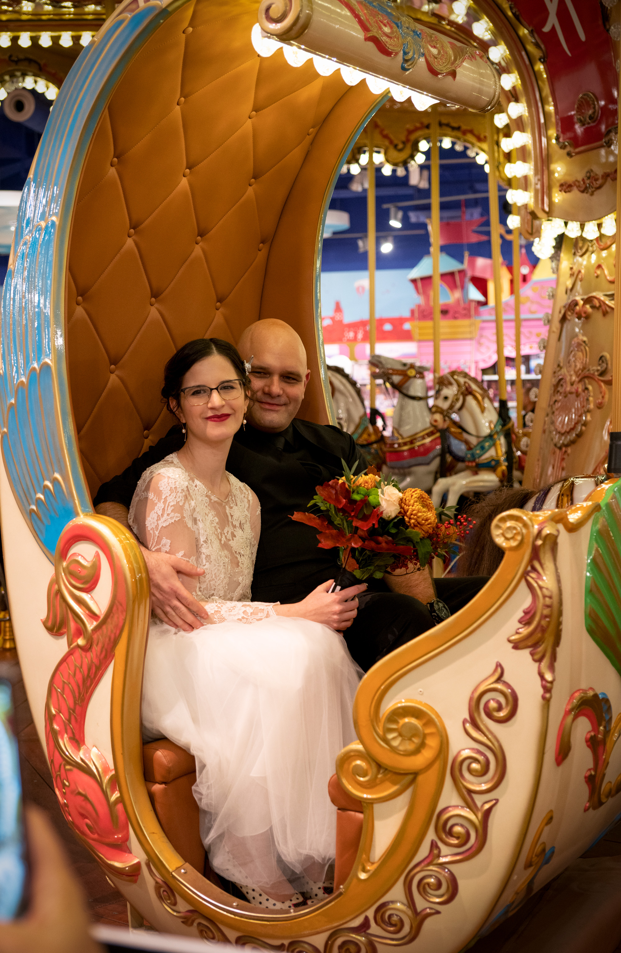Bride and groom on a carousel carriage with lights