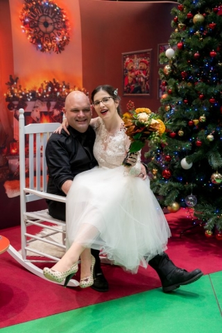 Bride and Groom on chair with Christmas tree